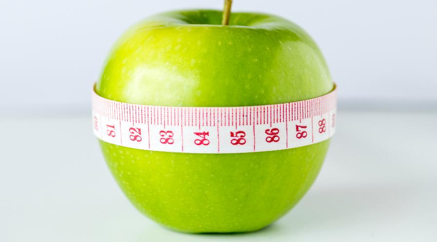 Zielone jabłko owinięte miarką centymetrową.