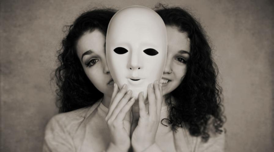 Zdjęcie czarno białe dwie te same kobiety tak jakby połączone stoją obok siebie. Kobieta z lewej ma smutną twarz, kobieta z prawej uśmiechnięta. Na wysokości głowy pomiędzy twarzami trzymają w ręku białą maskę.