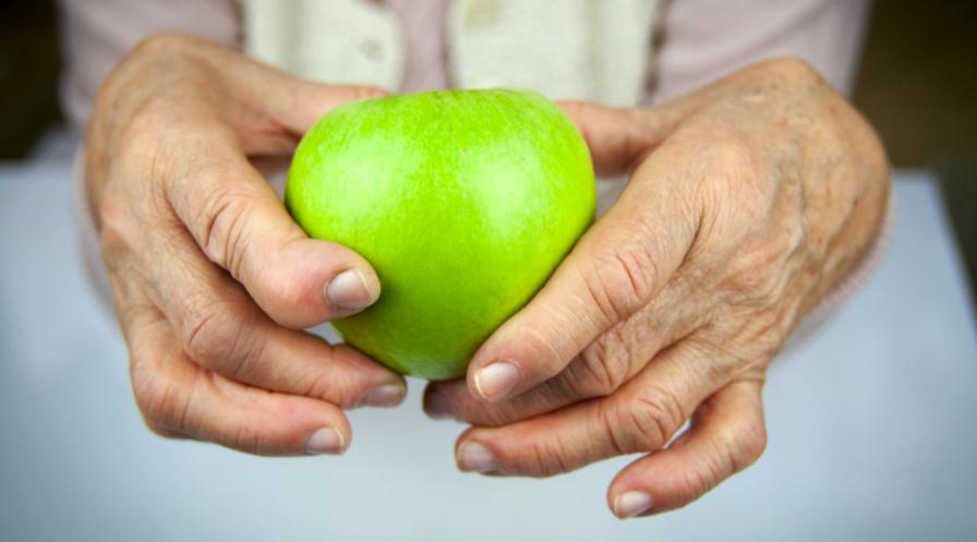 Zielone jabłko trzymane w dłoniach seniora z powykrzywianymi palcami.